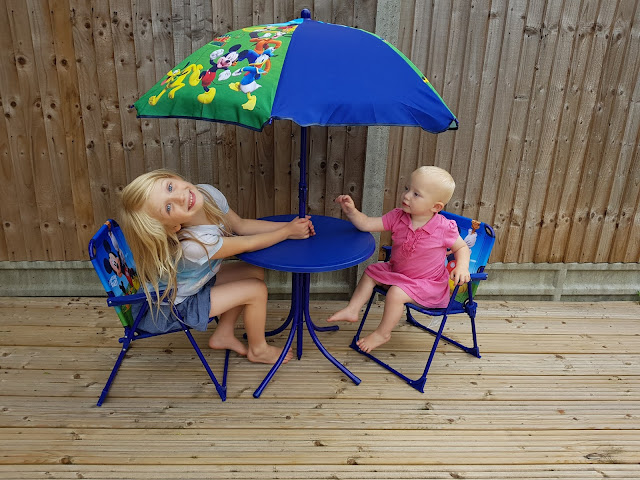 A blue Disney Mickey Mouse children's garden table, chairs and umbrella with 2 girls sitting at it