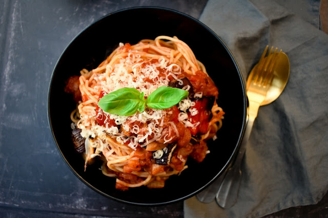 A black bowl full of spaghetti coated in homemade tomato and roasted red pepper pasta sauce
