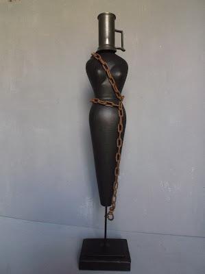 Escultura de madera, estaño y hierro, técnica de ensamblaje. Representa el sufrimiento de las mujeres en todo el mundo en la actualidad.