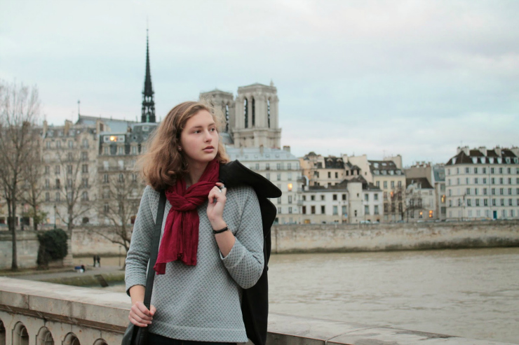 Parisian style of black pea coat, fashionable sweatshirt and jeans with a black leather bag