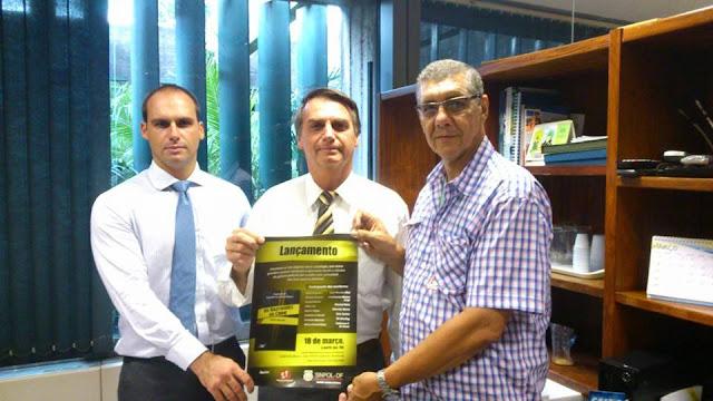 Eduardo Bolsonaro, Bolsonaro e Lindoberto Ribeiro segurando o cartaz de lançamento da antologia Os Bastidores do Crime