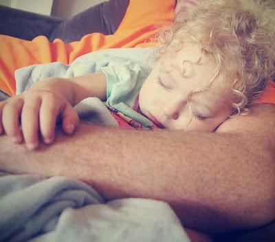 Kind schläft im Arm der Eltern