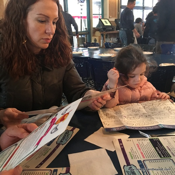 child and mother study menu at La Gloria in the Pearl in San Antonio, Texas