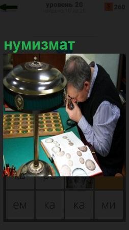 За столом сидит нумизмат мужчина и рассматривает свою коллекцию через лупу