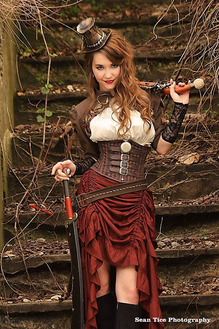 woman wearing steampunk clothing consisting of a red high low hem skirt, white blouse, brown bolero jacket and corset, black lace arm warmers, necklace and boots.