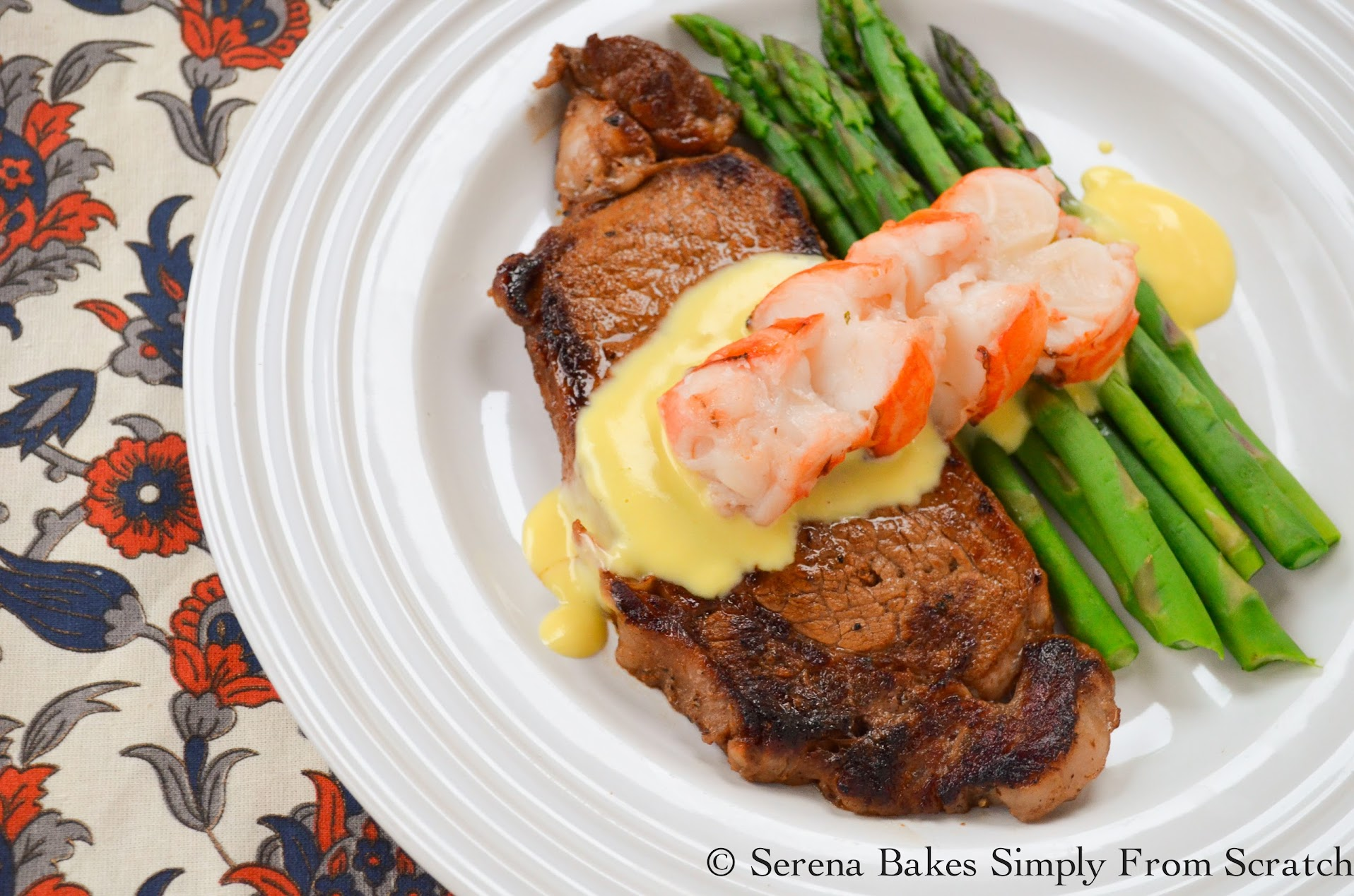 Perfectly Pan Seared Steak With Hollandaise Sauce and Lobster Tail served with a side of asparagus.