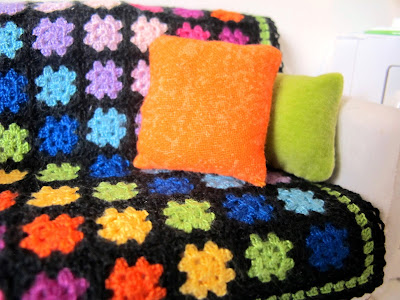 Modern dolls' house miniature rainbow crocheted afghan rug and bright cushions on a white sofa.
