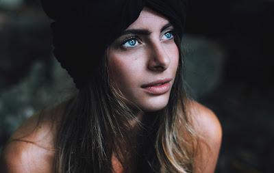 Chica de ojos azules mirando a la nada con gorro
