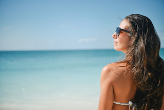 Sunglasses on girl at beach while wearing sunscreen