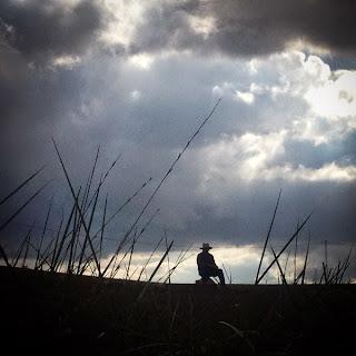 Sintiendo la gran paz de la tierra y observando  a las pacientes nubes que se acercan a la sierra  me pregunto: ¿Cuántas personas habrán olvidado  lo que es estar sentado en silencio en el campo  y el olor a tierra mojada que trae la tormenta?