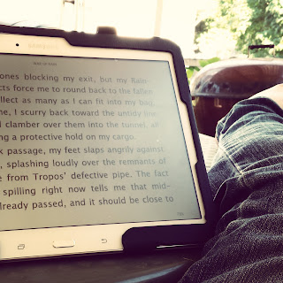 A tablet with the kindle program opened on it, sitting on top of a green plastic lawn table.