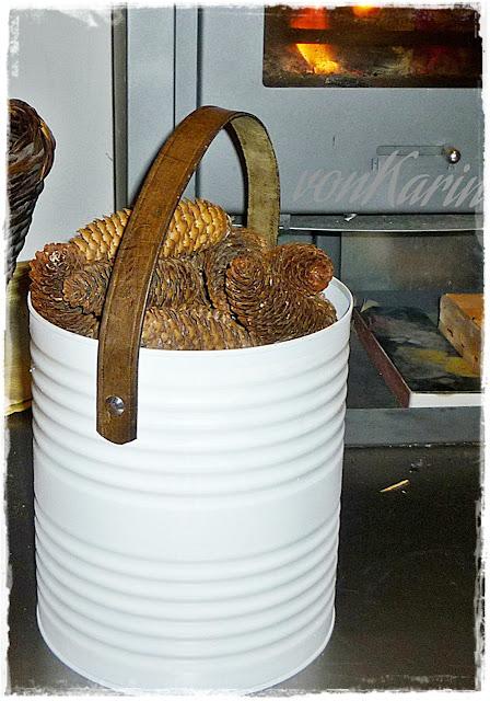 weisse grosse Konservendose mit Lederhenkel, gefuellt mit Fichtenzapfen