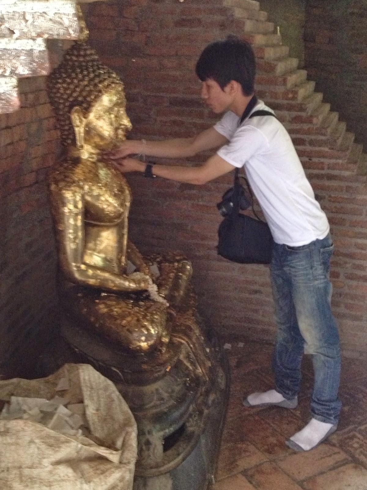 Ayutthaya - Wat Yai Chai Mongkhon - Temple visitors apply small gold leaf squares to Buddha statues