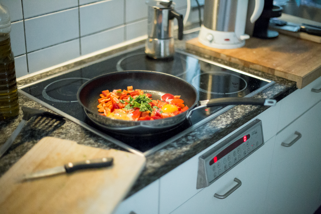 Vegetables sauteeing in a frying pan on a stove
