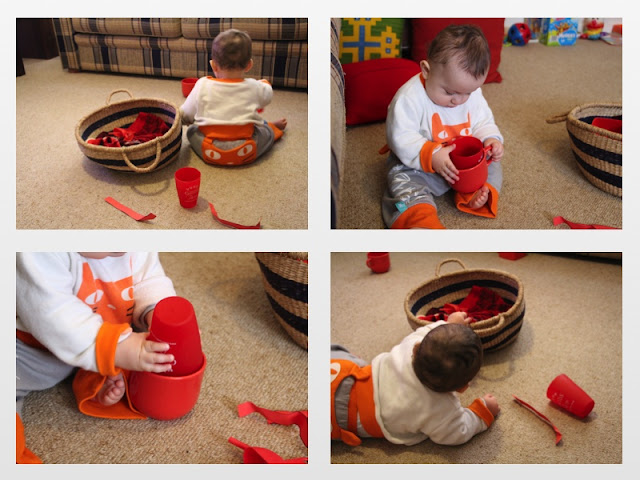 Baby playing with red treasure basket