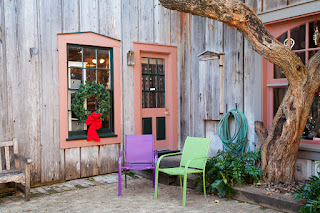 A corner shop with pastel colored trim has purple and green chairs out front, including a holiday wreath, in Salado, Texas