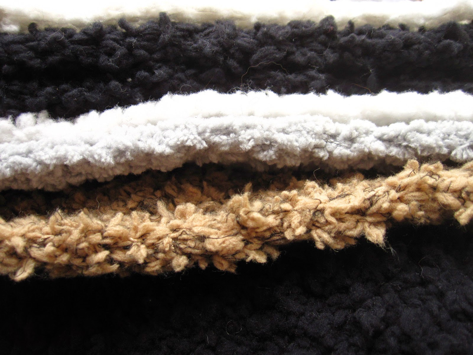 Stack of modern dolls' house miniature fluffy rugs in white, grey, black and fawn.