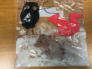 winter animal sensory ziplock bag filled with artificial snow and foam shape owl, mouse, and squirrel
