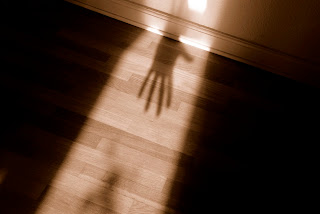 Illustration of the invasive nature of rape using shadows of a hand in a lighted outline of a person.