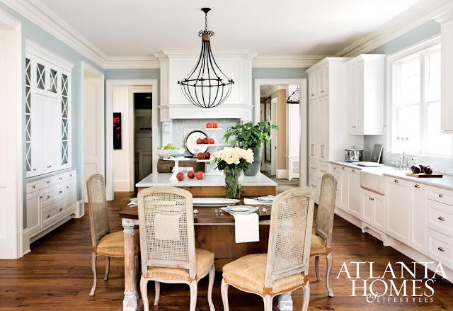 White kitchen with traditional style, blue walls, and vintage cane dining chairs
