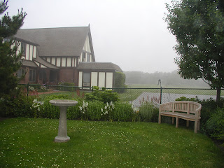 Large mansion overlooking a pond on a misty morning