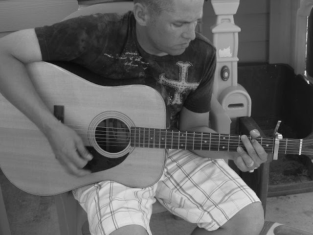 The author, Joe Stone, sits on a lawn chair strumming his guitar.