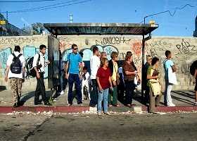 People waiting at a bus stage.