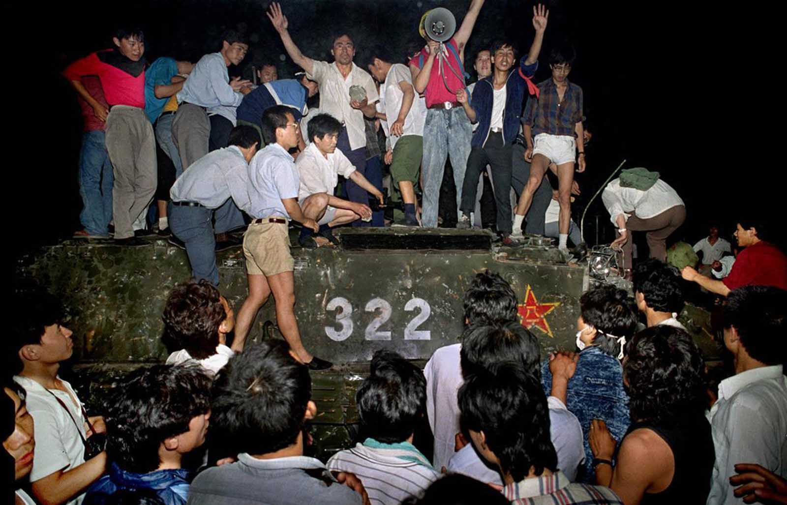 Civilians hold rocks as they stand on a government armored vehicle near Chang'an Boulevard in Beijing, early on June 4, 1989. Violence escalated between pro-democracy protesters and Chinese troops, leaving hundreds dead overnight.