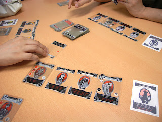 A table with several Gloom cards on it, the hands of some of the players visible as they reach for the various cards.