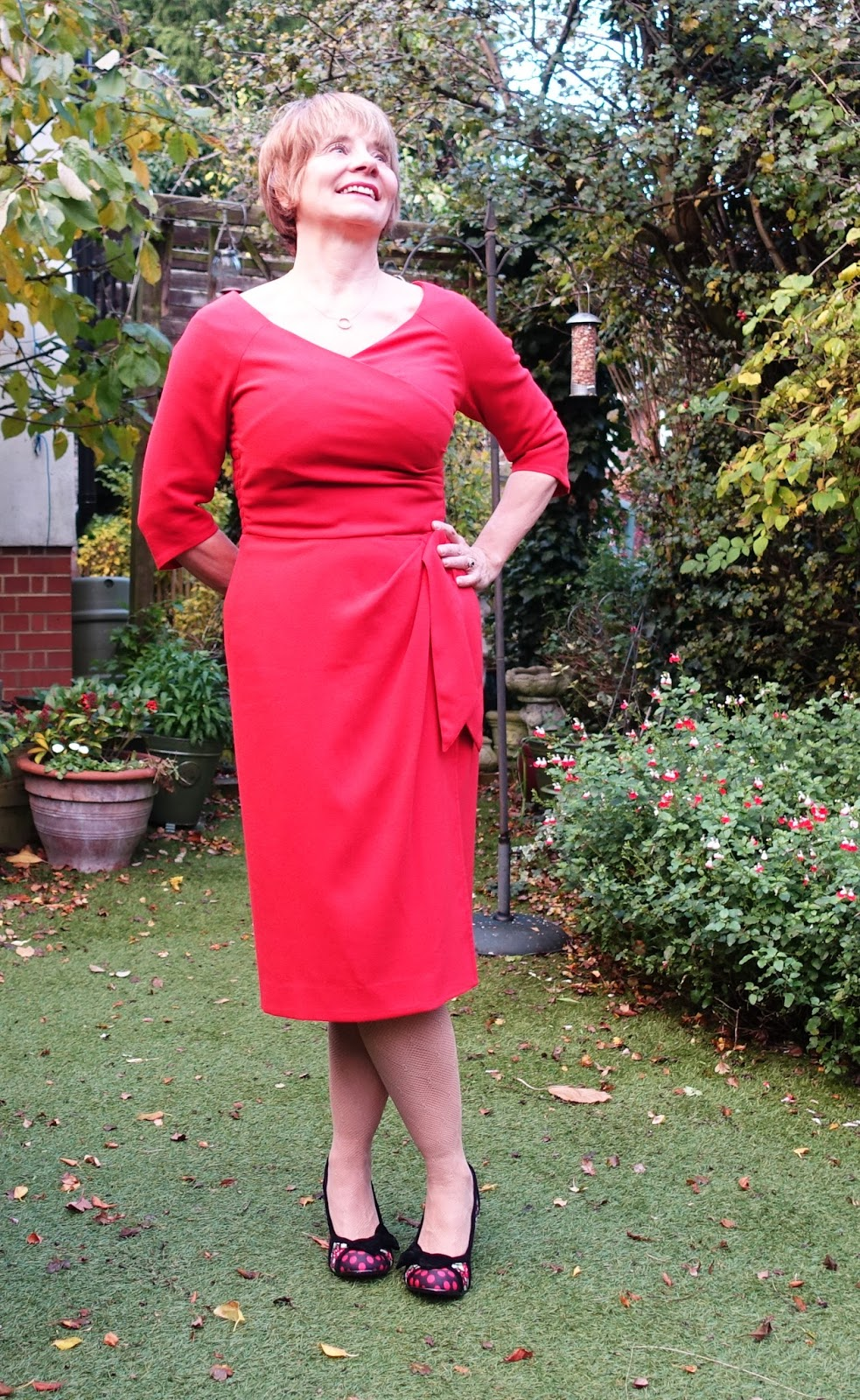 Image showing a 50 plus woman in red figure flattering dress and quirky red and black shoes decorated with cherries