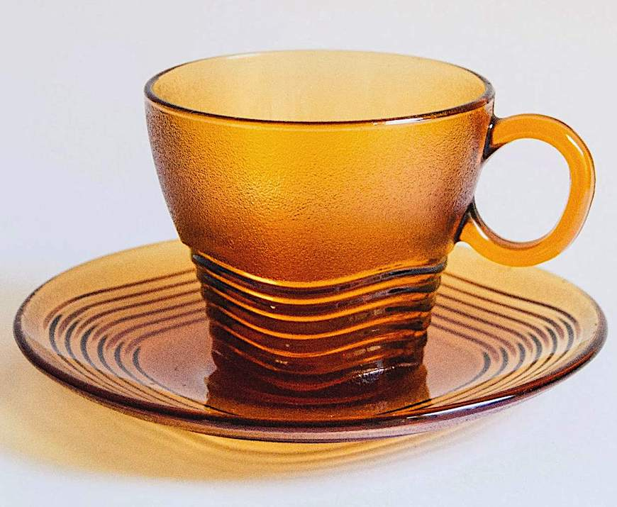 an amber glass cup & saucer, a color photograph