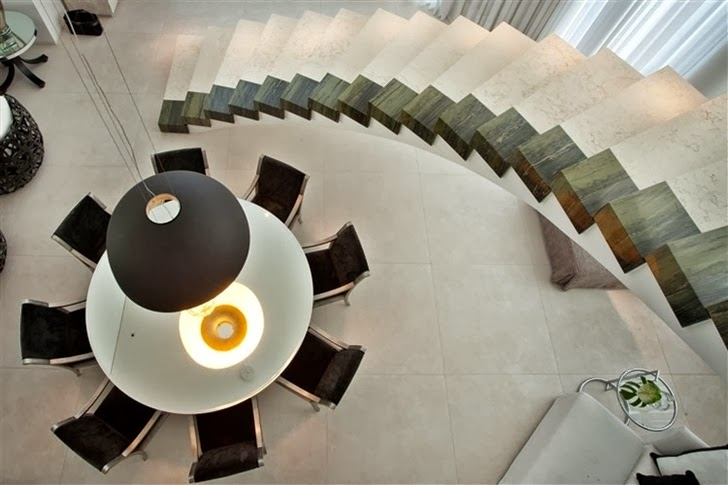 Table and stairs in Dream home by Pupo Gaspar Arquitetura