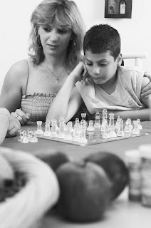 Concerned mom and distraught son study a chess board at a kitchen table.