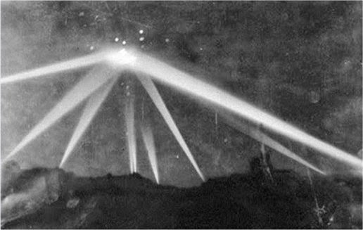 Spotlights focus on unidentified object above Los Angeles on February 25, 1942. The bright point flashes around the area it was a blast anti-aircraft guns.