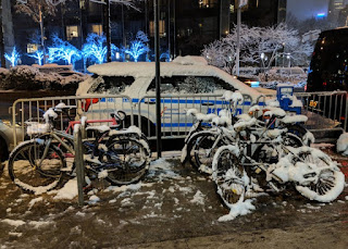 Snow covered bicycles, NYPD SUV, and bare trees, New York, New York