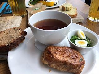 Skål med mørk suppe, flankert av brød, skål med purre og egg, og en liten pai.