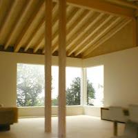 木立の中に建つ一体の屋根で結ばれた礼拝堂と木造住宅