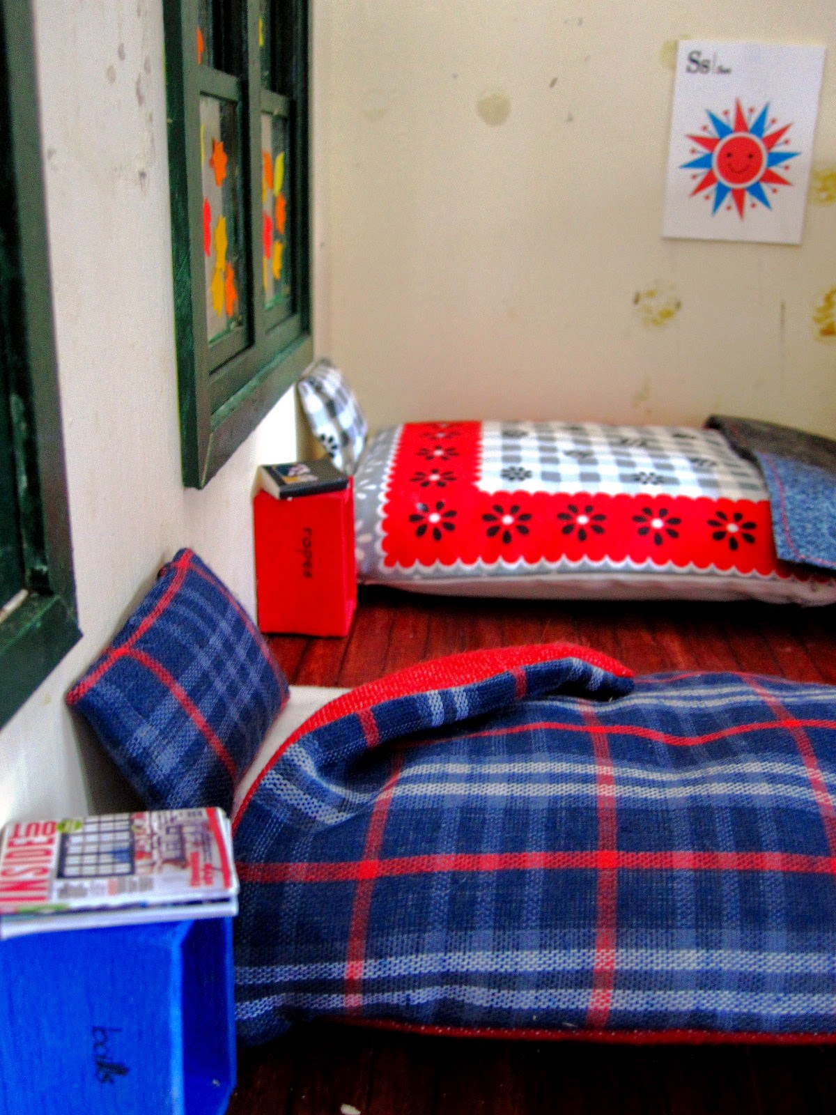 Miniature holiday house scene showing two mattresses on the floor, made up with sheets, pillows and doonas. Next to each is a wooden box on end with reading material on them.