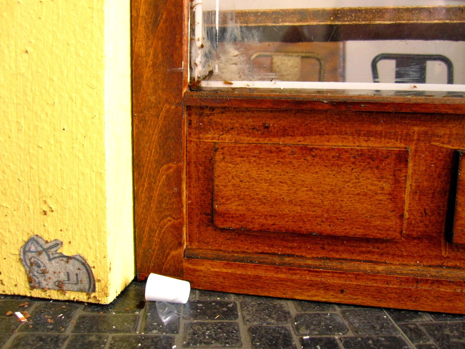Modern dolls' house miniature cafe exterior detail showing rubbish on the footpath and a paste-up on the wall.
