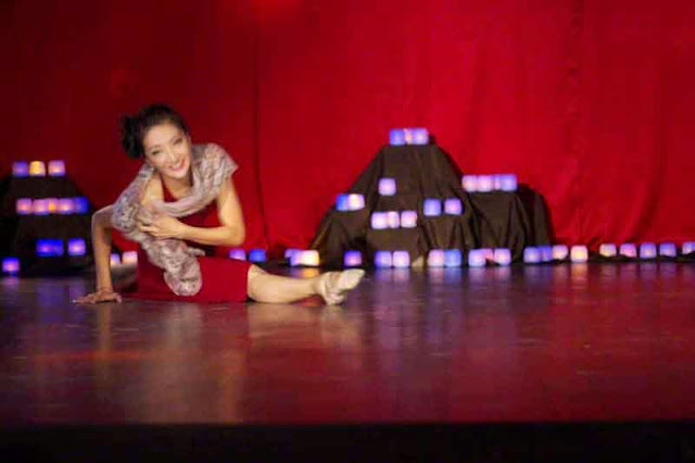 ballet dancer does split on candle lighted stage