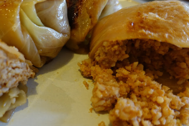 Rolled up parcels of white cabbage, one is cut open with a rice and pork mixture tumbling out on to a white plate