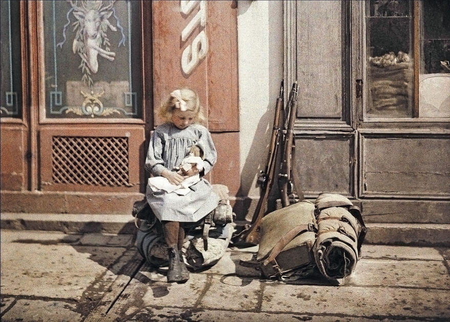 40 Old Color Pictures Show Our World A Century Ago - A Girl Holds A Doll Next To Soldiers' Equipment In Reims, France, 1917
