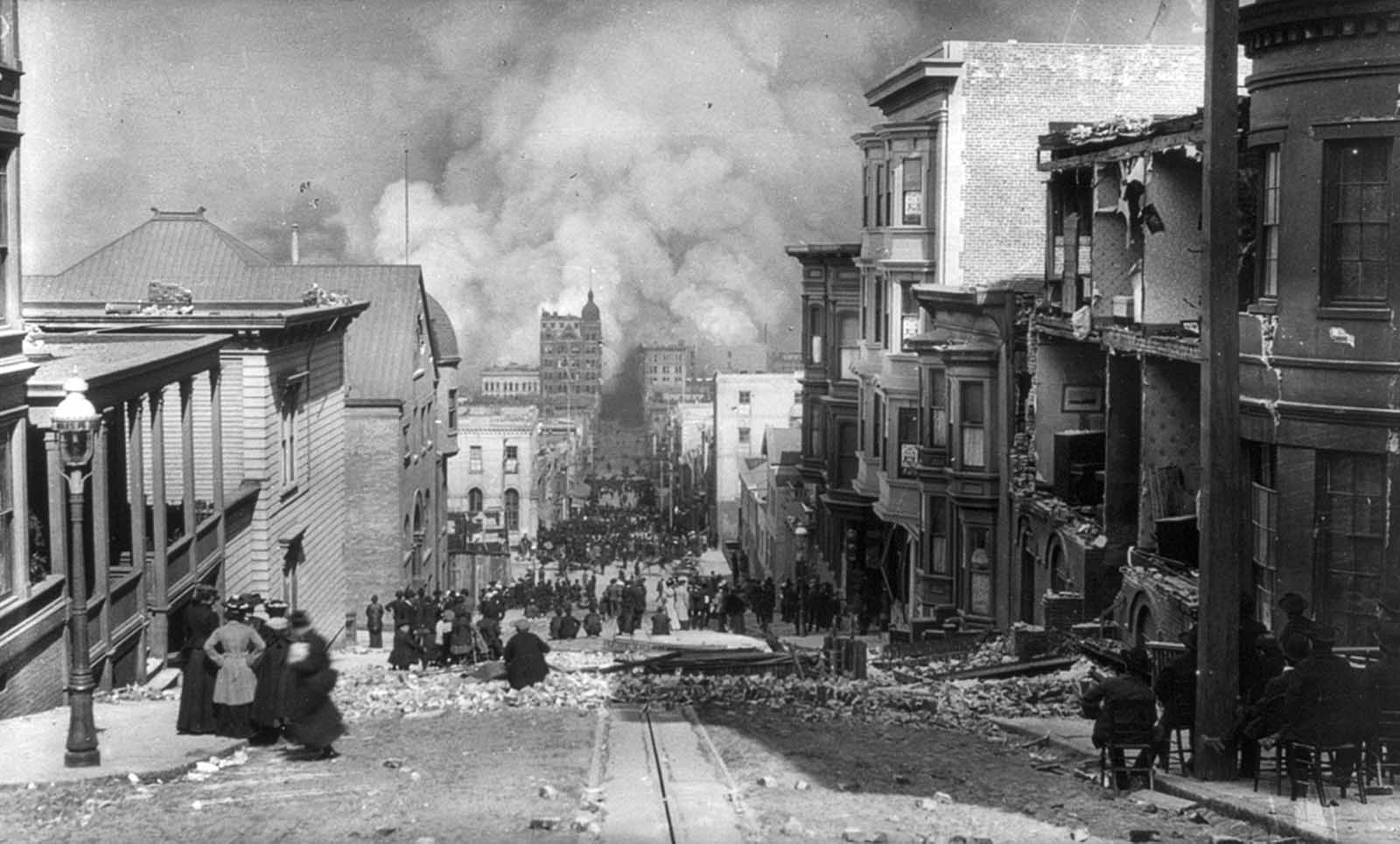 San Francisco residents, some seated in chairs, sit among the earthquake damage, watching out-of-control fires in the distance.