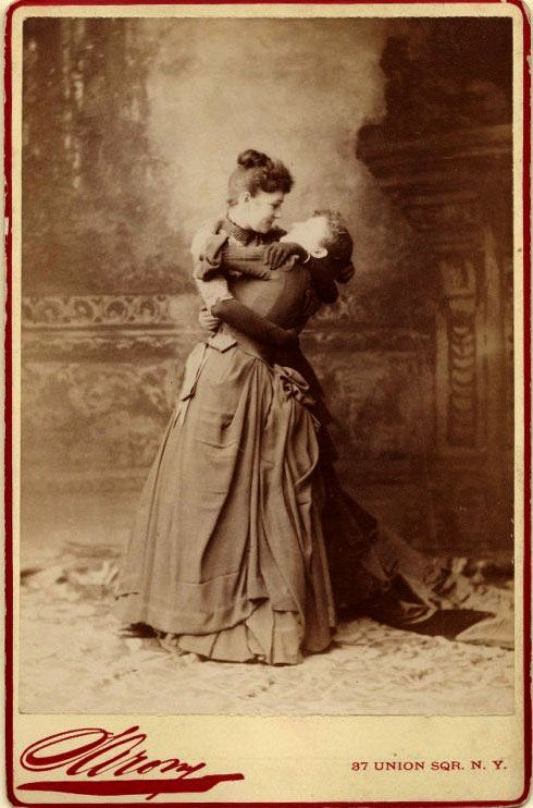 Two Victorian ladies laugh while in an embrace. Frighten the Horses. marchmatron.com