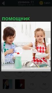 Девочка моет посуду, а помощник мальчик ей в этом помогает