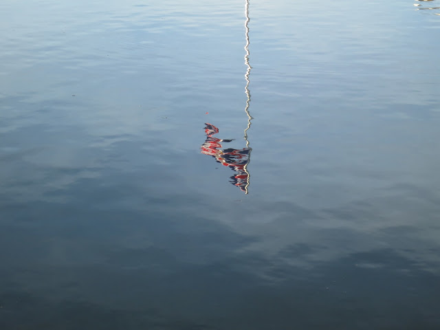 Reflection of Union Jack in water running into harbour at West Bay in Dorset