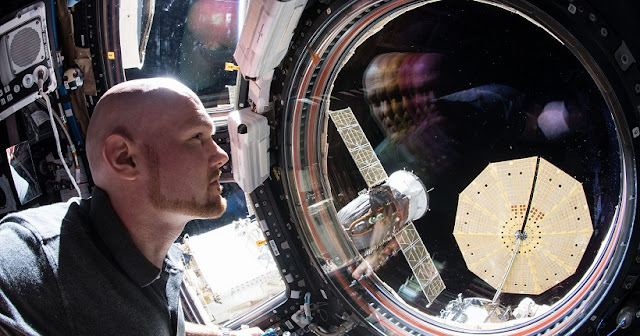 "Expedition 57 Commander Alexander Gerst of ESA (European Space Agency) peers out the International Space Station's ""window to the world,"" the seven-windowed cupola. Just outside the cupola are two spacecraft including the Soyuz MS-09 crew craft and Northrop Grumman's Cygnus cargo craft with one of its cymbal-shaped UltraFlex solar arrays featuring prominently in the frame. Credit: NASA"