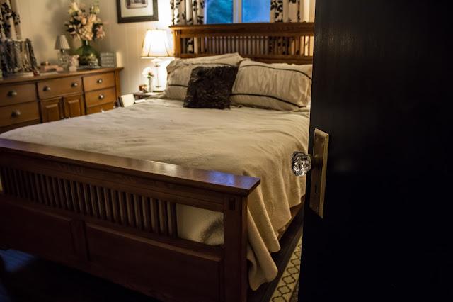 Black door with glass knob to the bedroom