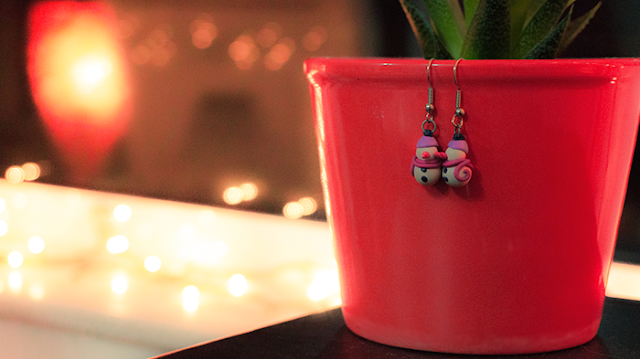 A pair of snowman earrings hanging from a flower pot and christmas light on the background.