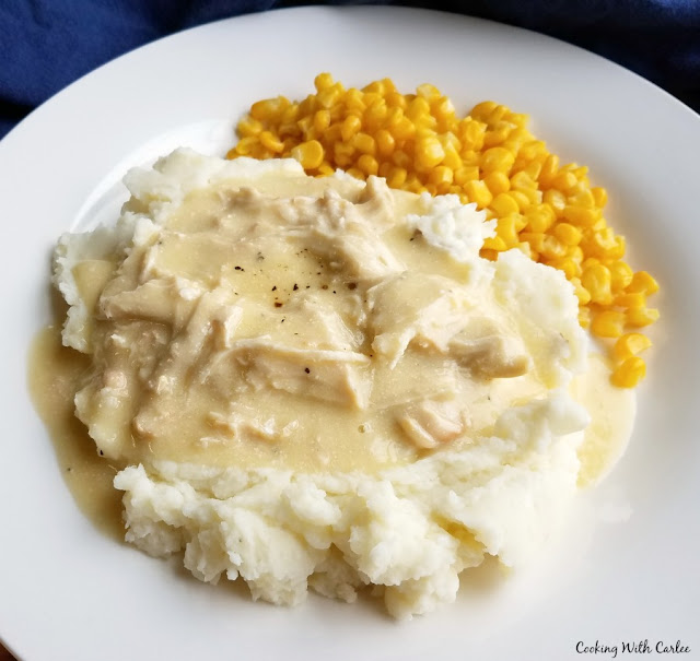 plate with cream chicken on top of mashed potatoes with corn on the side
